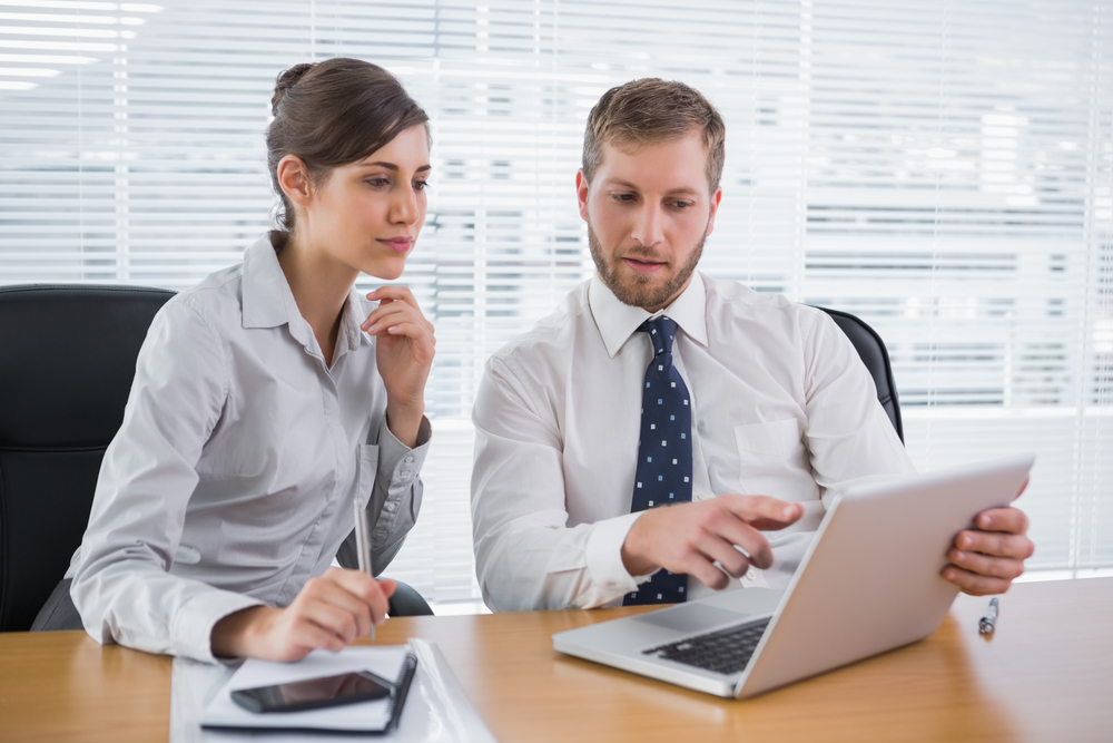 Business people working together on laptop in office at desk